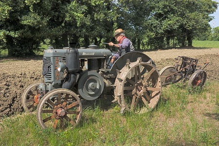 BASTIA, RAVENNA, ITALY - MAY 29: unidentified man plow the field with an old tractor during ricordando i vecchi tempi recall of the old farm work, on May 28-29 2011 in Bastia, Ravenna, +.-