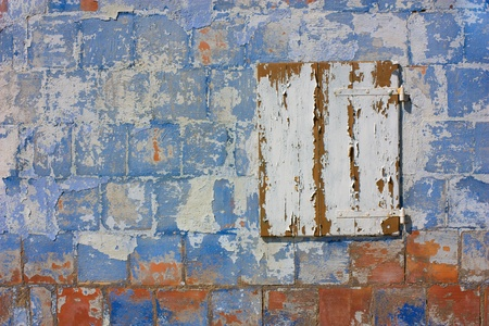 dirty old wall with peeling paint and white closed window - scratched plaster - urban decay - grunge colored texture Stock Photo