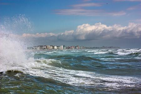sea storm, waves crashing on the cliff of italian coast photo