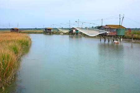 ravenna: fishing huts - shacks with net on the river of ravenna, italy