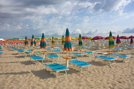 beach with umbrellas and sunbeds under a cloudy sky - a deserted bathing at dawn  Stock Photo - 10419803