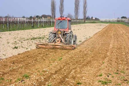 harrow: farmed land view - harrow for soil preparation - field with agricultural tractor preparing the ground for sowing
