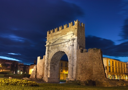 intact: night view of Augustus arch in Rimini - ancient romanesque gate of the city - historical landmark of Italy, the most ancient roman arch that still stands intact