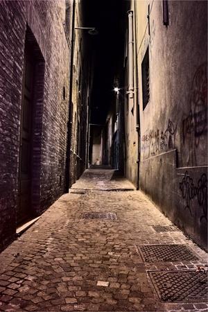 krottenwijk: Italiaanse vuile smal steegje 's nachts - donkere decadente straat in de oude stad