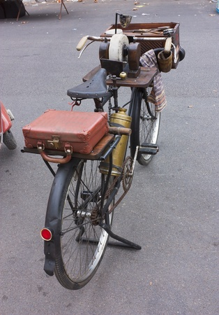 sharpening: bicycle for peddler knife grinder  both transportation and power supply for his work are furnished by the bicycle; a chain that connects his bicycle wheel to his grinding stone; thanks to the mechanism the grindstone rotates as he pedals his