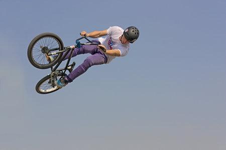 bmx bicycle freestyle - stunt biker make a jump on blue sky background at Ferrara balloons festival on September 17, 2011 in Ferrara, Italy