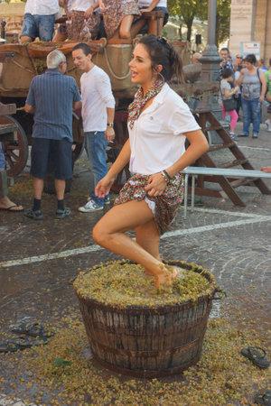 Traditionelle Zubereitung des Mostes für die Weinproduktion, ein Mädchen erdrückt die Trauben mit den Füßen während des Festivals von typisch italienischen Wein am 2. Oktober 2011 in Cotignola (RA), Italien Standard-Bild - 10793270