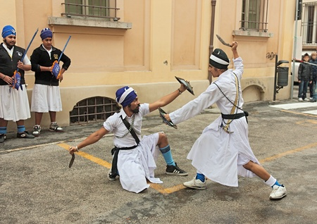 indians Sikh in traditional costume performing a knife duel with an old fighting weapon at Fiera di San Rocco, festival that hosts historical recalling and various performance and exposition, on November 6, 2011 in Faenza, RA