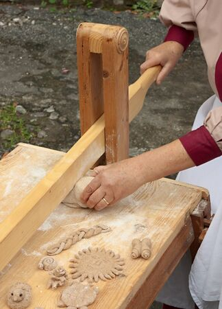traditional goods: artisan baked goods from Italy: woman making the dough for bread with a traditional italian wooden tool called gramadora