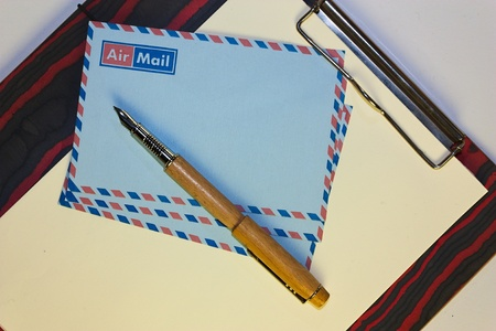 clipboard with letter paper - airmail envelopes and fountain pen - correspondence with foreign photo