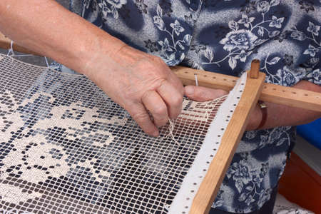 elderly woman making an embroidery with the wooden frame - handmade traditional needlework  photo
