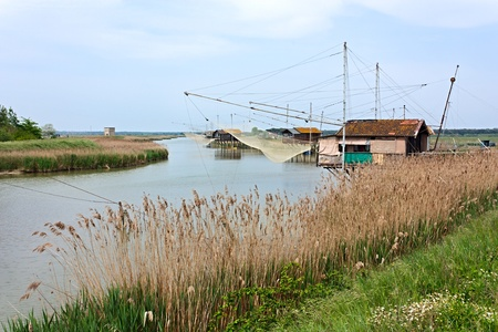 ravenna: shacks on the boat with fishing net in the river of ravenna