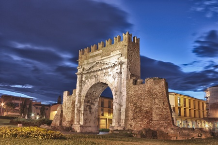 intact: night view of Augustus arch in Rimini - ancient romanesque gate of the city - historical landmark of Italy, the most ancient roman arch that still stands intact - HDR image