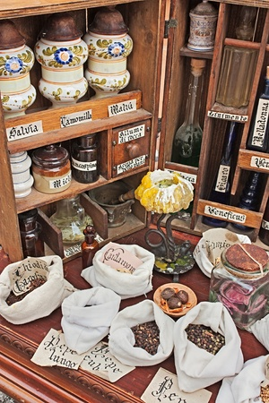 reproduction of antique pharmacy with officinal herbs, spices and venomous substance - medicinal plants on canvas sacks for alternative medicine