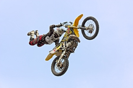 freestyle motocross show: a stunt biker make a jump and performing an acrobatic figure in flight, during the motorcycle rally Motosalsicciata 2012 on March 25, 2012 in Voltana di Lugo (RA) Italy