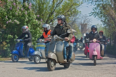 a group of bikers riding a vintage italian  scooters Lambretta and Vespa at motorcycle rally of local Vespa Club on April 9,2012 in Santarcangelo di R. (RN) Italy