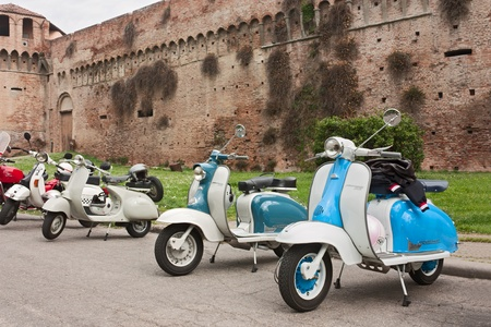 vintage italian scooters Lambretta and Vespa near at the castle at motorcycle rally on April 29, 2012 in Imola (BO) Italy