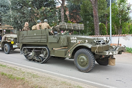 soldiers aboard an old half-track military vehicle at historical reenactment of World War II The column of liberation 2012 on April 29, 2012 in Zello, Imola BO, Italy