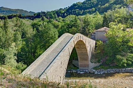 appennino: ancient humpback bridge in Castel del Rio, Bologna, Italy - six centuries old arch bridge over the italian river Santerno