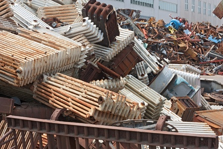 scrap heap: metallic waste storage for recycling - old heating radiators of cast iron and other metals refuse