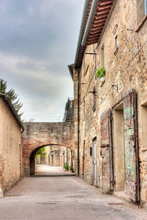 old narrow alley with arch in tuscan village  - antique italian lane in San Quirico d photo