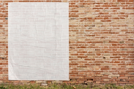 old poster: blank street advertising billboard stuck on brick wall - empty white sheet of paper - copy space in poster glued on wall - copyspace