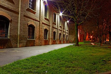 industrial park: narrow alley at night in the italian old town - dark street and old industrial buildings in Italy Editorial