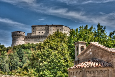 emilia romagna: medieval fortress on the italian hills - landscape with castle and church in San Leo, Rimini, Italy  Editorial