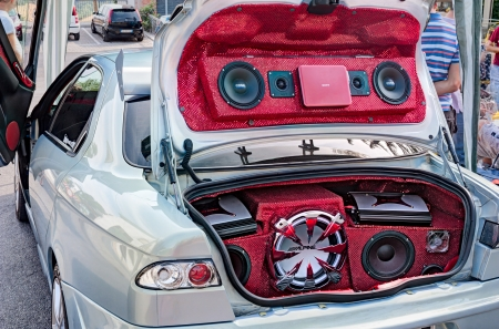 power music audio system with amplifiers, bass and treble speakers in the car trunk exhibited at rally Fashion tuning club, on August 12, 2012 in Borghi, RN, Italy
