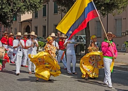 street parade of ensemble Jocaycu from Colombia with national flag - colombian dancers in traditional dress performs popular dance during the International folk festival on August 5, 2012 in Russi, Ravenna, Italy