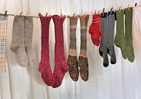 calcetines: viejos calcetines de lana hechos a mano que cuelgan a secar Foto de archivo