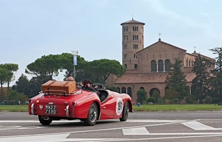 reenactment re enactment: vintage racing car Triumph TR3 A (1960) passes in front of the famous Basilica of Sant