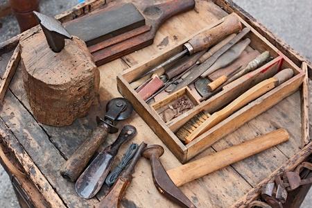 riparatore: tavolo da lavoro con i vecchi strumenti del calzolaio artigiano Archivio Fotografico