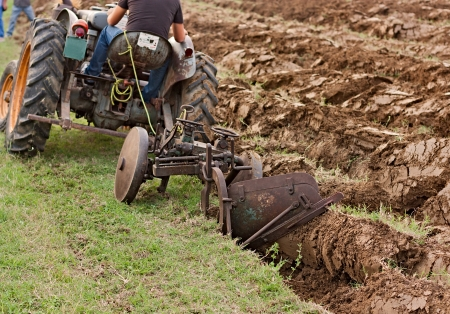 plough land: plowing the field with an old tractor and plow Stock Photo