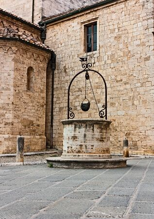 nook: antique water well in the picturesque nook of italian old town Castiglione d Stock Photo