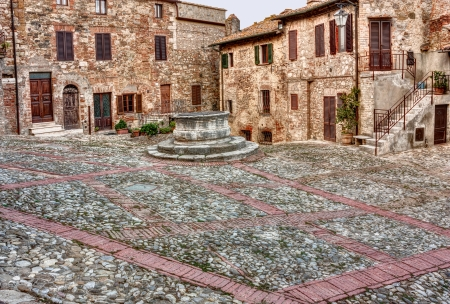 old square with water well in the italian old town Castiglione d photo