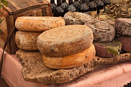 ripe sheeps milk cheese on a piece of cork and bottles of Italian wine in background - traditional artisan food product  from Sardinia, Italy