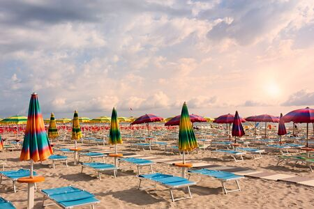 beach with umbrellas and sunbeds under a cloudy sky - a deserted bathing at dawn Stock Photo - 16587281