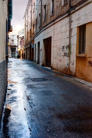 narrow alley in the old town - dark street after the rain  photo