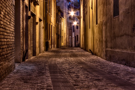 street corner: narrow dark alley in the old town - street at night in the Italian city