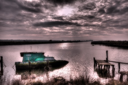 landscape with lonely abandoned boat in the river at morning, under a dramatic cloudy sky photo