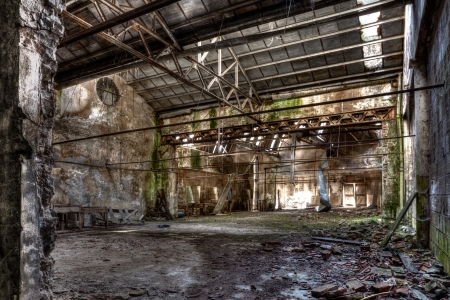 hdr: interior of abandoned factory with rubble and debris - desolate room of an old destroyed industrial warehouse - hdr image