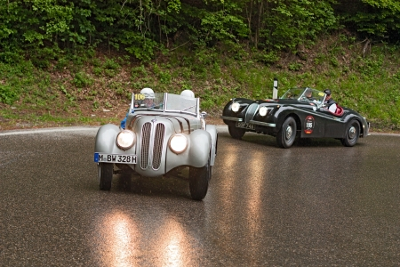 reenactment re enactment: an old racing car BMW 328 (1939) runs before Jaguar XK 120 OTS  (1953) in rally Mille Miglia 2012, re-enactment of the old italian endurance race (1927-1957) on May 19, 2012 in Passo della Futa (FI) Italy Editorial