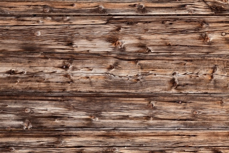 old rustic plank of knotty wood -  background texture of cracked wooden board