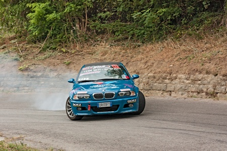 swerve: a drift racing car BMW in action with smoking tires in hairpin bend at rally Predappio legend 2012, historical italian uphill race, on July 21, 2012 in Predappio, FC, Italy Editorial