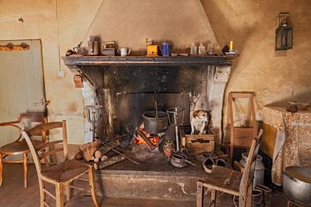 cocina antigua: interior de una antigua casa de campo donde un perro se pone caliente en el interior de la chimenea Foto de archivo