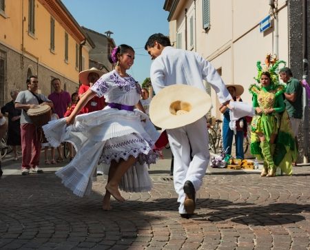 wooing: ensemble Imagenes de Peru - couple of peruvian dancers in white dress performs traditional courting dance la marinera at International folk festival on August 5, 2012 in Russi, Ravenna, Italy