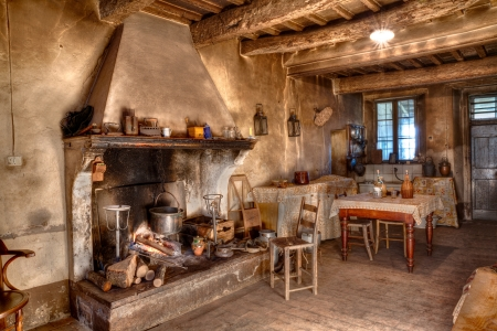 rustic kitchen: old times farmhouse - interior of an old country house with fireplace and kitchen Editorial