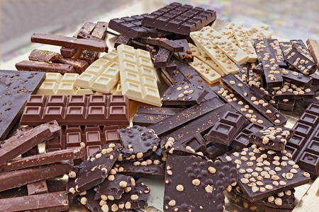 pile of assorted chocolate bars - heap of black and white chocolate pieces with hazelnuts photo