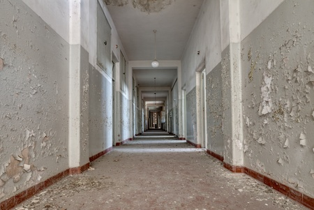 forsaken: interior of an abandoned building with rubble and debris - desolate corridor of an old hospital Stock Photo